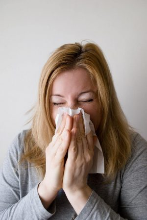 woman blowing nose from allergens
